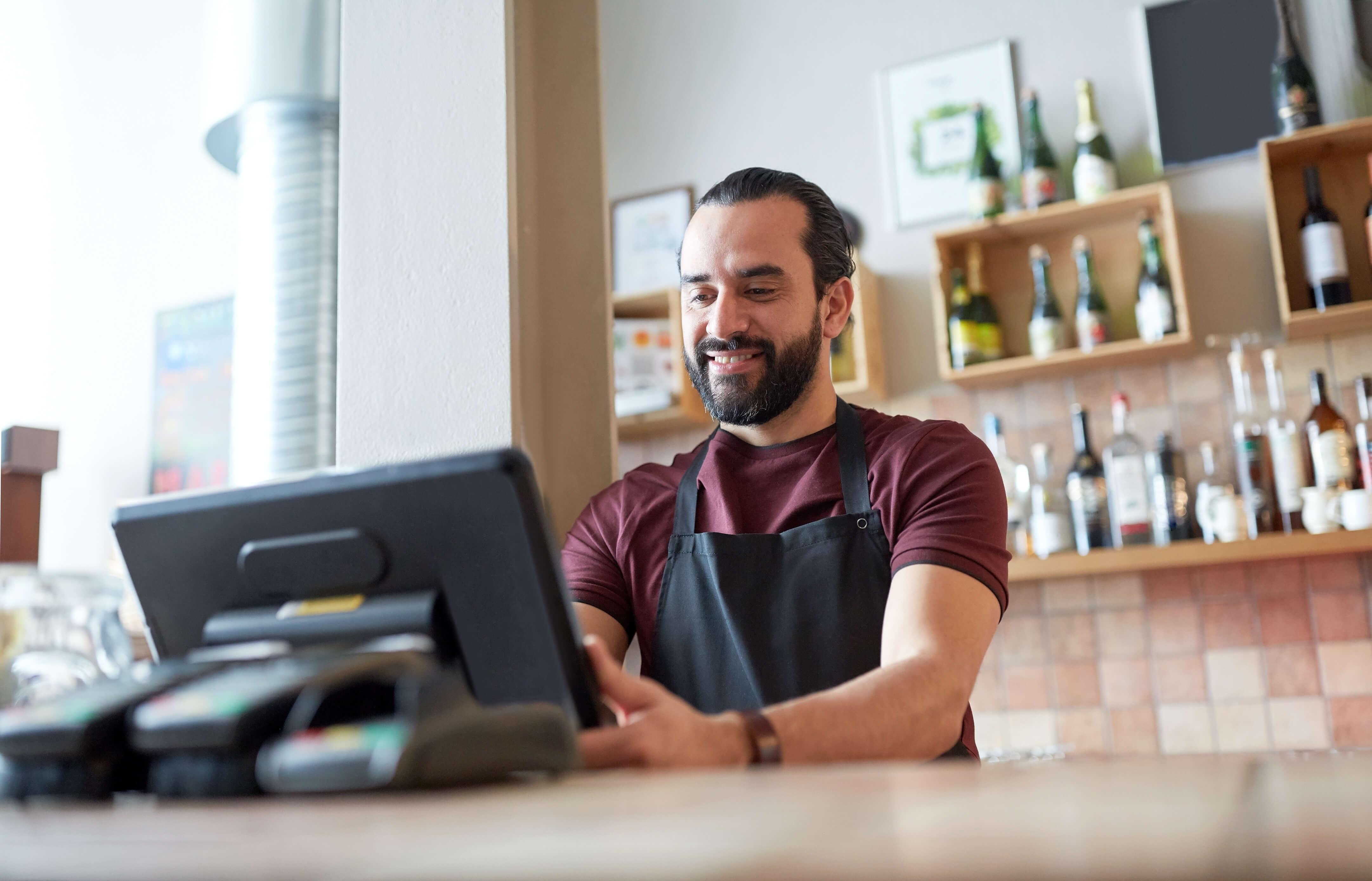 Happy man behind counter